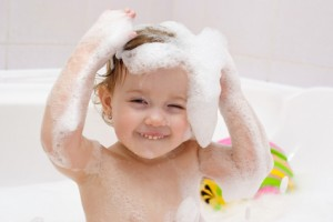 cute baby is washing her hair in bath